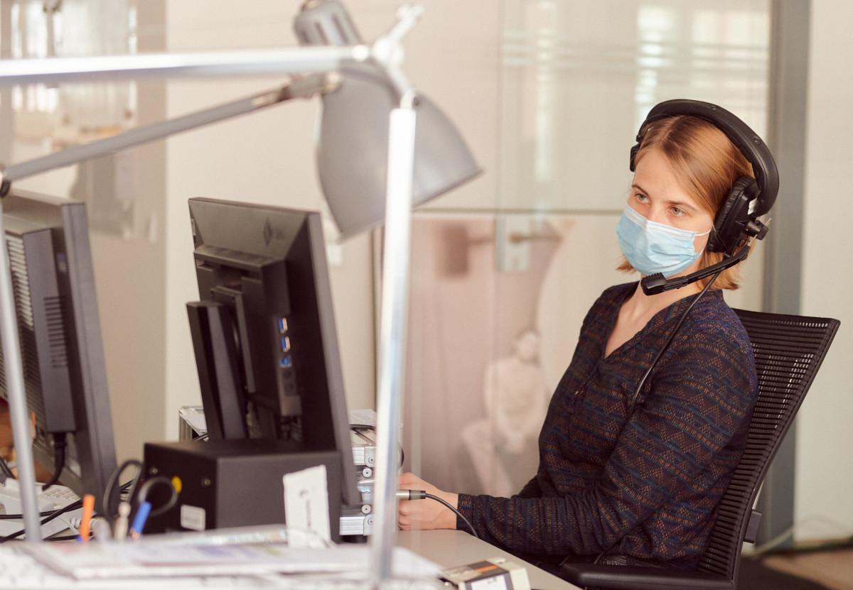 Redakteurin und Produktmanagerin Jennifer Knappheide, mit Atemschutzmaske, führt das Interview über einen Monitor im Großraumbüro der ZEIT Akademie.