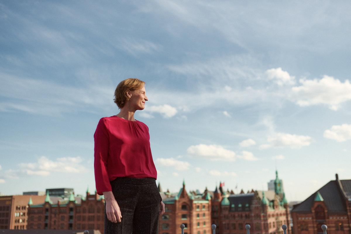 Purpose-Beraterin Julia von Winterfeldt schaut in die Ferne, im Hintergrund Häuser